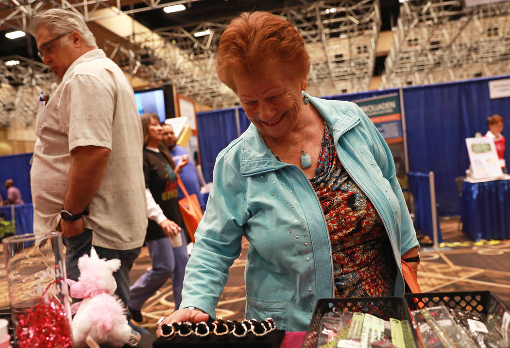 Maria Demeo looks at jewelry from Paparazzi during the AgeWell Expo at the Rio Convention Center in Las Vegas on Saturday, April 14, 2018. Andrea Cornejo Las Vegas Review-Journal @dreacornejo