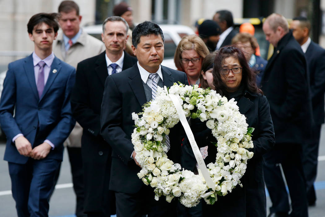 The father of Lingzi Lu Jun Lu foreground left and her aunt Helen Zhao foreground right carry a wreath ahead of the family of Martin Richard background from left Henry Bill Denise and Jan