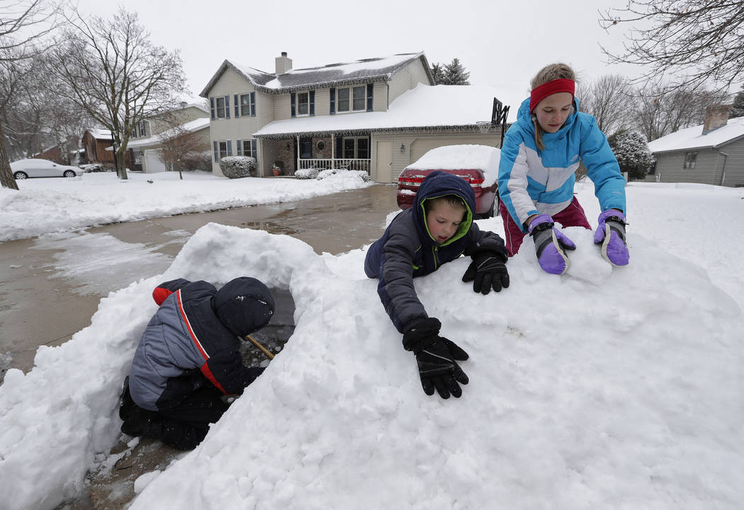 Bryce Rosenau, 13, left, makes a snow fort with his brother Blake, 10, and sister Elise, 15, right, during a snowstorm Saturday, April 14, 2018, in Appleton, Wis. (Dan Powers/The Post-Crescent via AP)
