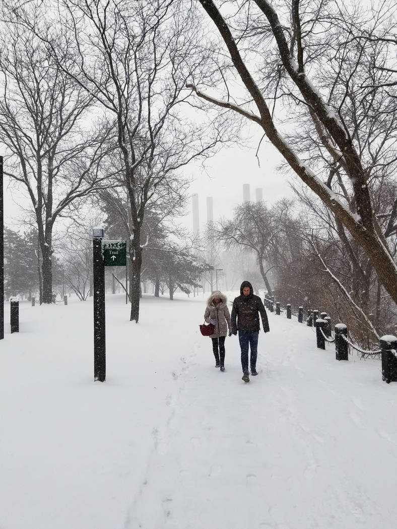 Niko Heiligman, of Aachen, Germany, and Lea Stimpel walk along the Mississippi River in downtown Minneapolis during a snow storm on Saturday, April 14, 2018. The National Weather Service predicts ...