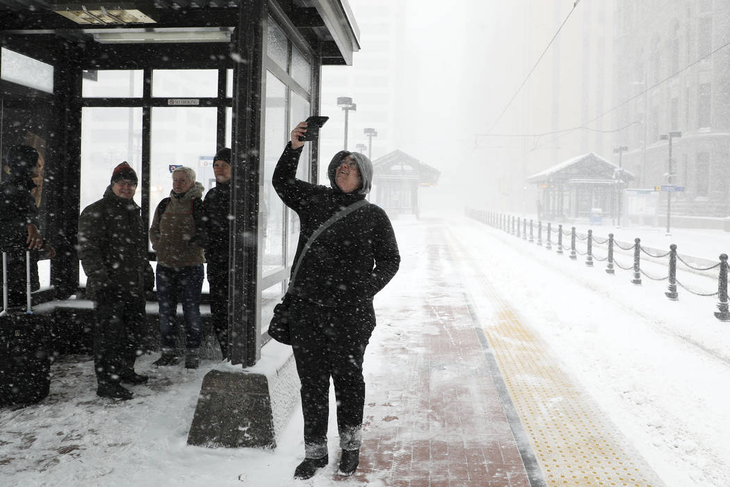 Travelers at the Metro Government Center Plaza station wait for a train as the snow picked up in downtown Minneapolis, Saturday, April 14, 2018. The National Weather Service predicts 9 to 15 inc ...
