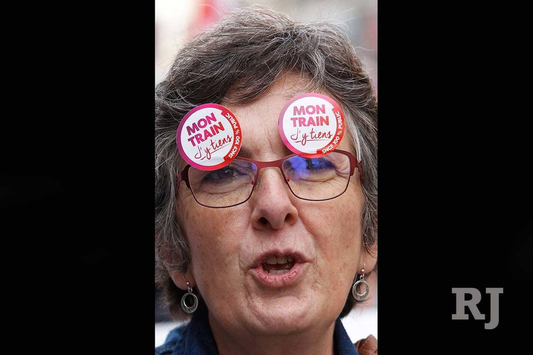 "A demonstrator stuck stickers on her glasses reading ""My train, I care"" during a march by rail workers protesting against French President Emmanuel Macron's government reforms, in Marseille, Franc ..."