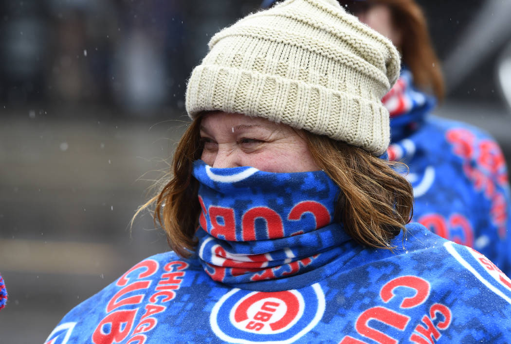 Barb Brauer keeps herself warm outside Wrigley Field after a baseball game between the Atlanta Braves and the Chicago Cubs was postponed on Sunday, April 15, 2018, in Chicago. The game is reschedu ...