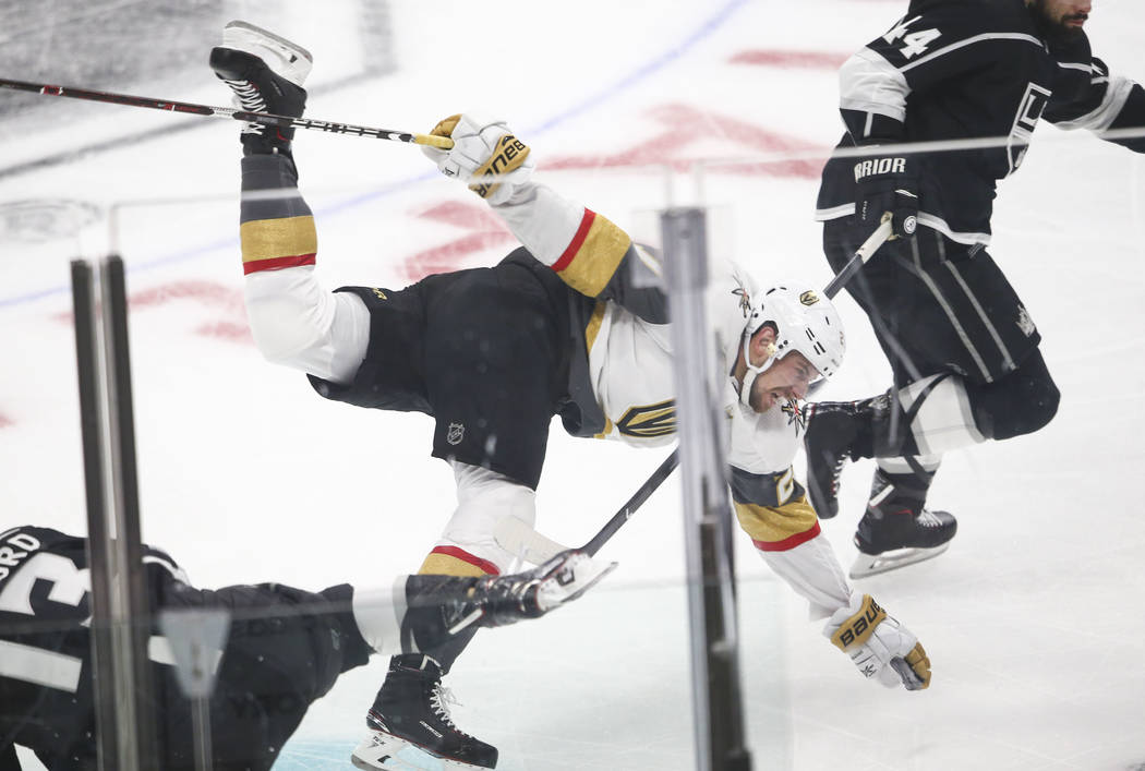 Golden Knights defenseman Shea Theodore (27) gets tripped by Los Angeles Kings left wing Kyle Clifford (13) during the first period of Game 3 of an NHL hockey first-round playoff series at the Sta ...