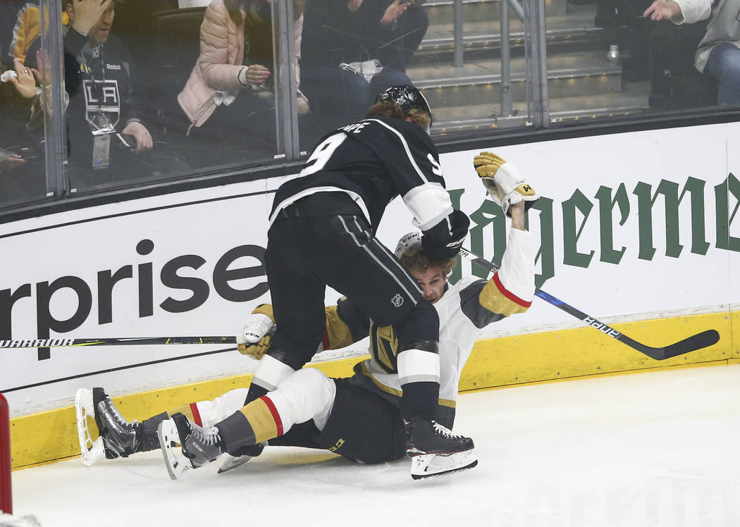 Golden Knights defenseman Jon Merrill (15) gets knocked down and hit by Los Angeles Kings left wing Adrian Kempe (9) during the first period of Game 3 of an NHL hockey first-round playoff series a ...
