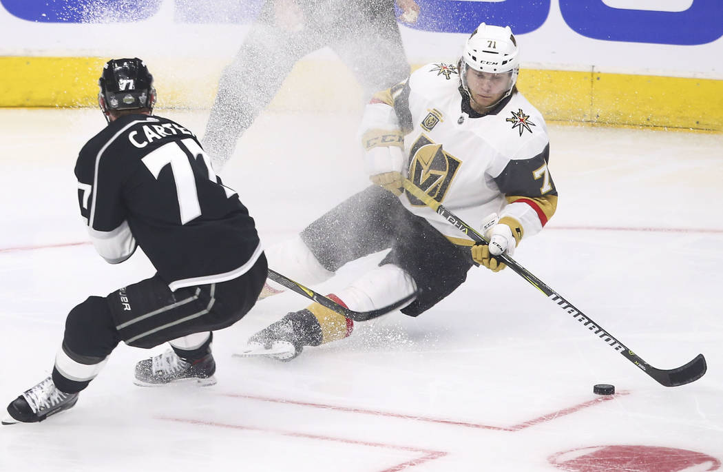 Golden Knights center William Karlsson (71) slips on the ice while moving the puck as Los Angeles Kings center Jeff Carter (77) defends during the second period of Game 3 of an NHL hockey first-ro ...