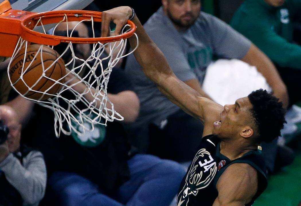 Milwaukee Bucks' Giannis Antetokounmpo dunks during overtime in Game 1 of an NBA basketball first-round playoff series against the Boston Celtics, in Boston, Sunday, April 15, 2018. The Celtics wo ...