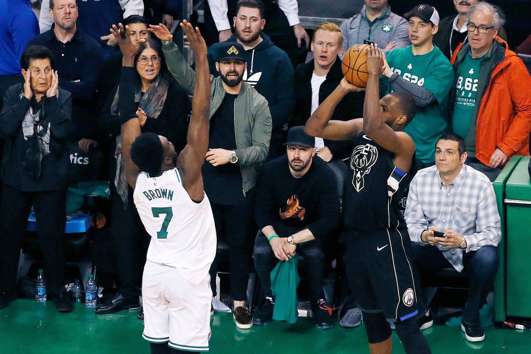 Milwaukee Bucks' Khris Middleton shoots a three-point basket over Boston Celtics' Jaylen Brown (7) with less than a second to play in the fourth quarter of Game 1 of an NBA basketball first-round ...