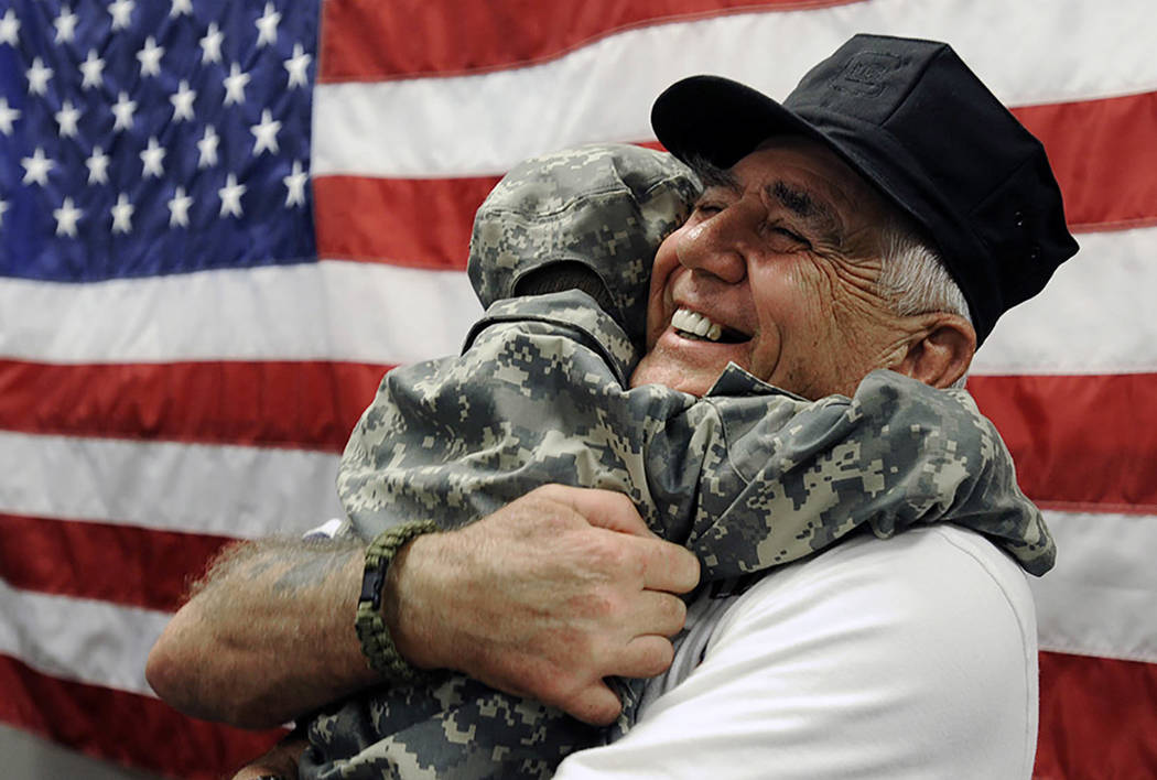 R. Lee Ermey gets a surprise hug from 4-year-old Bryant Teat, who ran up to Ermey and hugged him after Ermey signed an autograph in Hoover, Ala., in 2012. (Joe Songer/AL.com via AP, File)