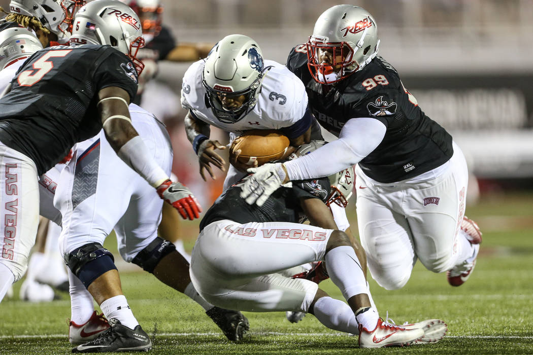 Howard Bison quarterback Caylin Newton (3) is tackled by UNLV defensive back Tim Hough (13) and defensive lineman Nick Dehdashtian (98) during the fourth quarter at Sam Boyd Stadium in Las Vegas, ...
