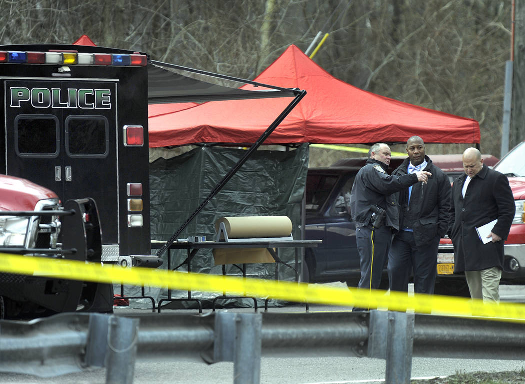Police work at the scene where a man and a woman were found slain in a pickup truck near the intersection of Routes 55 and 7, Thursday morning, April 12, 2018, in Gaylordsville, Conn. Authorities ...