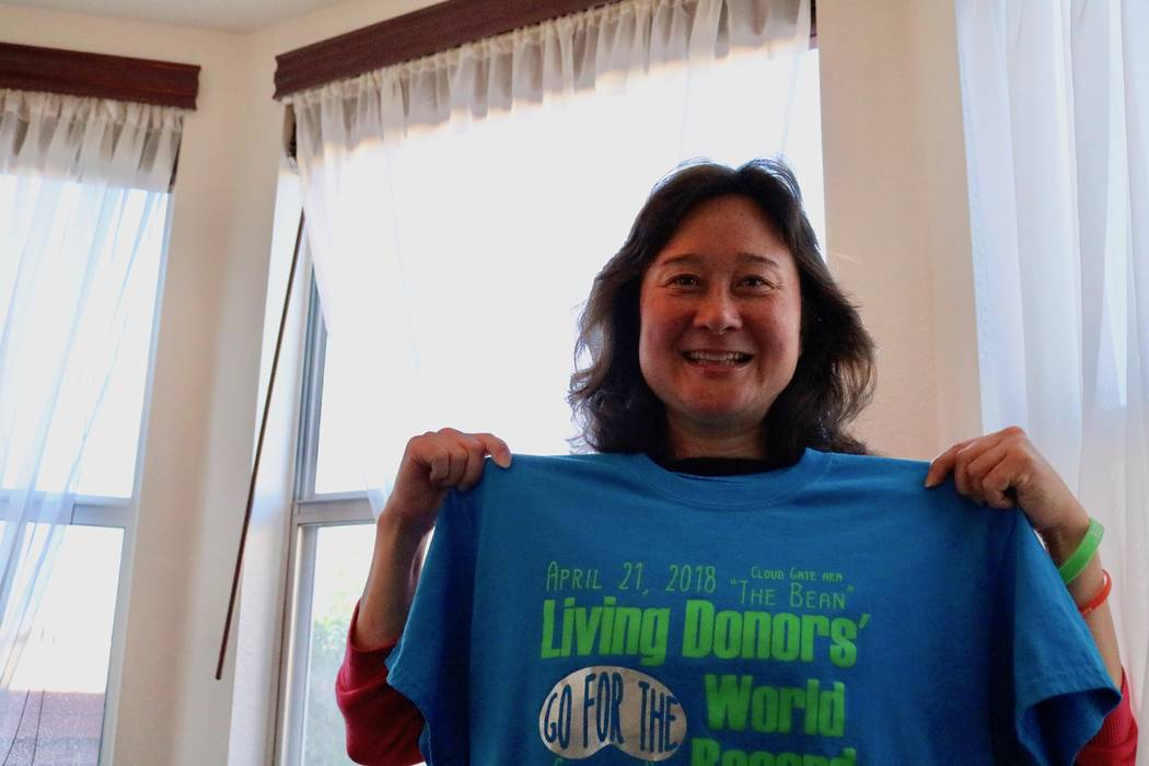 June Monroe shows off her living donors' world record shirt in her Las Vegas home on Thursday April 12, 2018. She'll join more than 250 living organ donors at the Cloud Gate sculpture in Chicago o ...