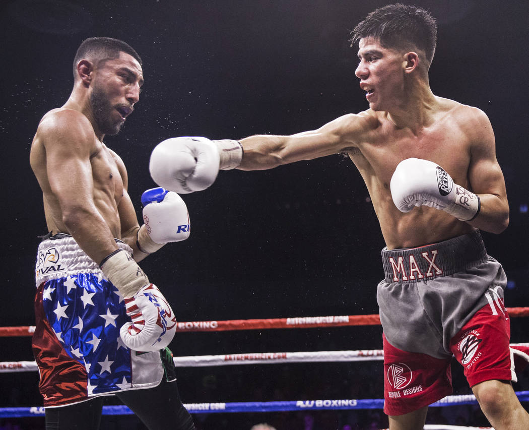 Max Ornelas, right, throws a right hook against Tony Lopez during their bantamweight boxing match on Friday, April 20, 2018, at Cox Pavilion, in Las Vegas. Ornelas defeated Lopez by unanimous deci ...