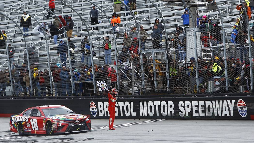 Kyle Busch celebrates with fans after winning a NASCAR Cup Series auto race, Monday, April 16, 2018, in Bristol, Tenn. (AP Photo/Wade Payne)