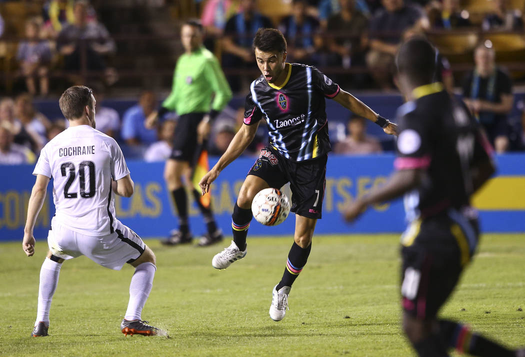 Las Vegas Lights FC midfielder Carlos Alvarez (7) kicks the ball past San Antonio FC defender Greg Cochrane (20) during the first half of a United Soccer League game at Cashman Field in Las Vegas ...