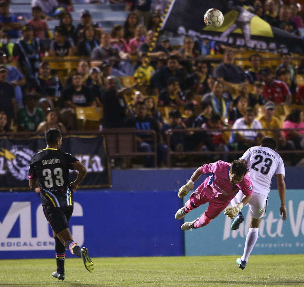 Las Vegas Lights FC goalkeeper Ricardo Ferrio (1) flies in the air to block a shot in front of San Antonio FC midfielder Jose Escalante (23) during the second half of a United Soccer League game a ...