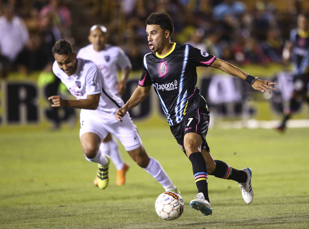 Las Vegas Lights FC midfielder Carlos Alvarez (7) moves the ball past San Antonio FC defender Ryan Felix (3) during the first half of a United Soccer League game at Cashman Field in Las Vegas on F ...