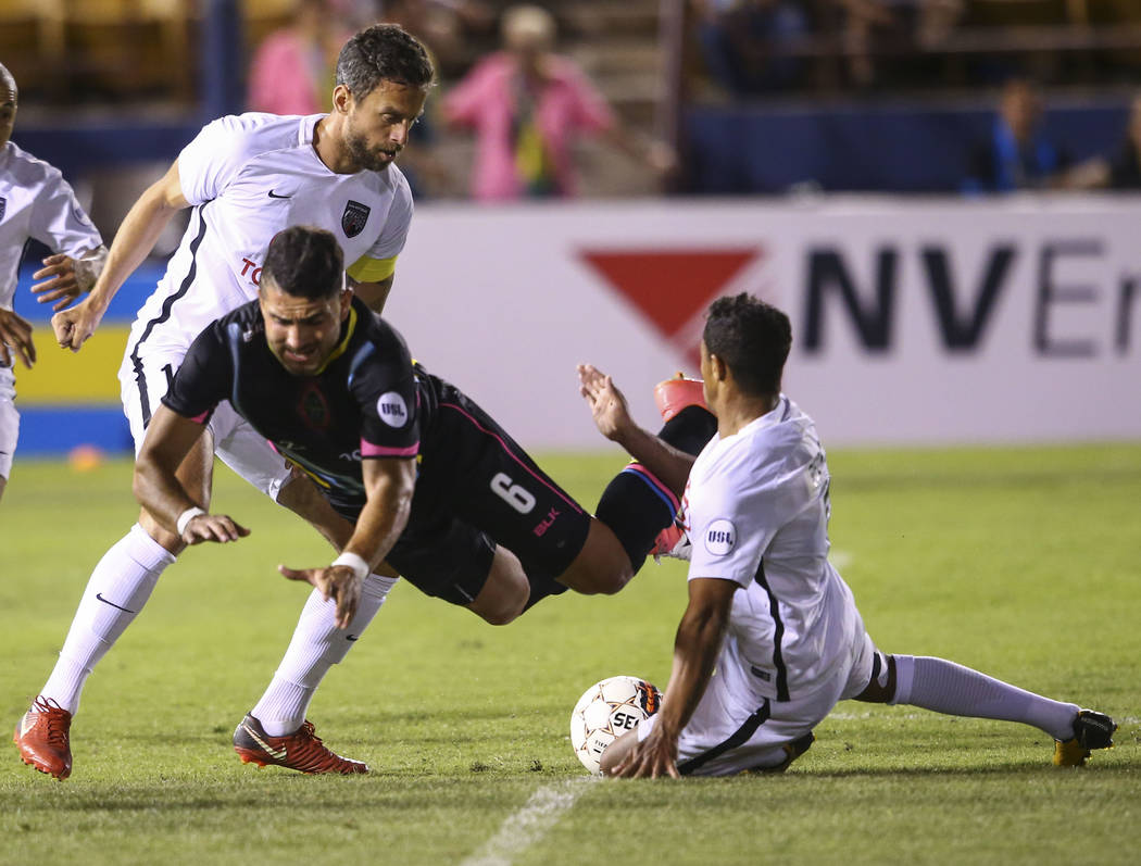 Las Vegas Lights FC defender Marco Cesar Jaime Jr. (6) gets tripped up between San Antonio FC midfielders Ryan Roushandel (11) left and Pecka (8) during the first half of a United Soccer League ga ...