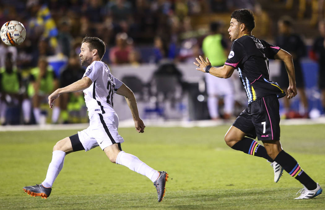 San Antonio FC defender Greg Cochrane (20) and Las Vegas Lights FC midfielder Carlos Alvarez (7) chase after the ball during the first half of a United Soccer League game at Cashman Field in Las V ...
