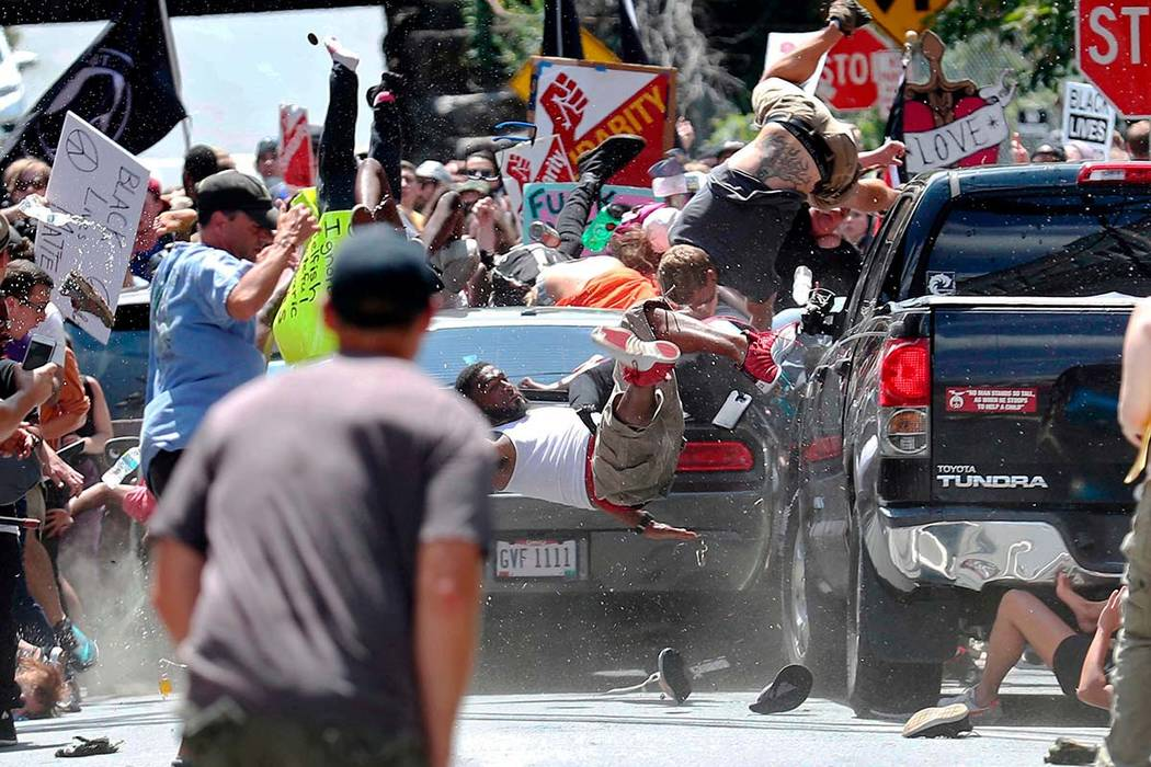 In this Aug. 12, 2017, photo by Ryan Kelly of The Daily Progress, people fly into the air as a car drives into a group of protesters demonstrating against a white nationalist rally in Charlottesvi ...