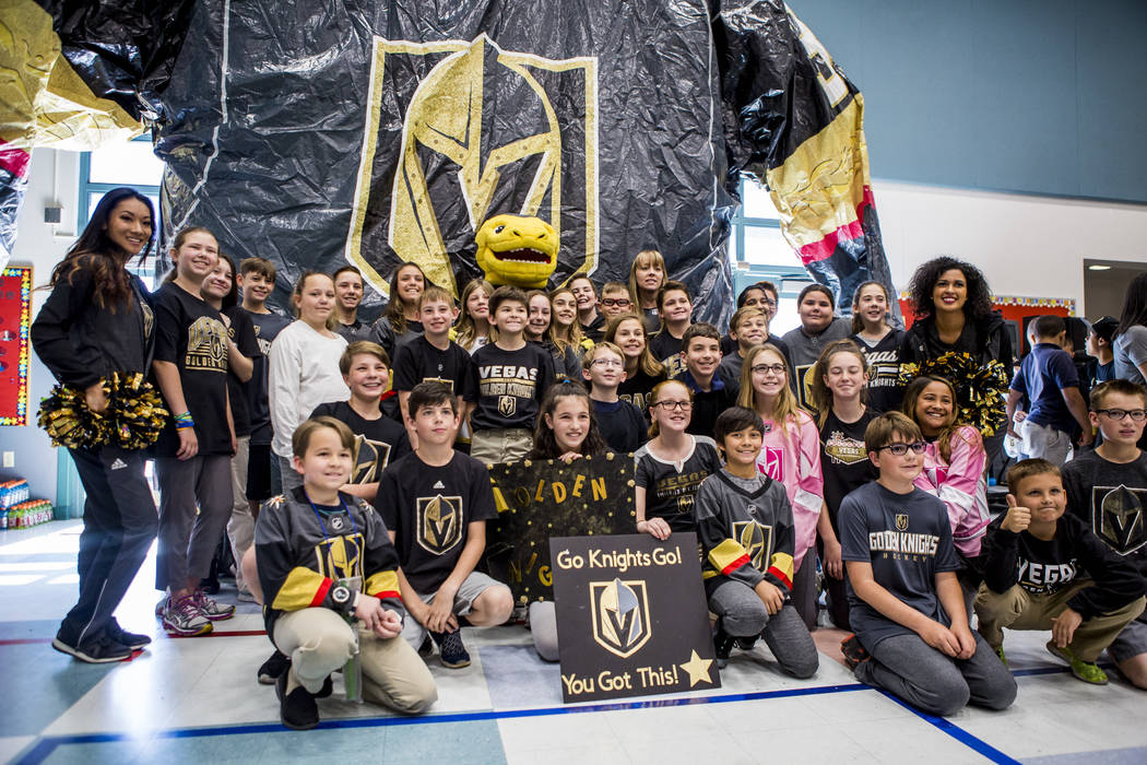 Vegas Golden Knights mascot Chance the Gila monster and Golden Aces cheerleaders come together for a group photo with elementary schoolers during a Golden Knights pep rally for fourth and fifth gr ...