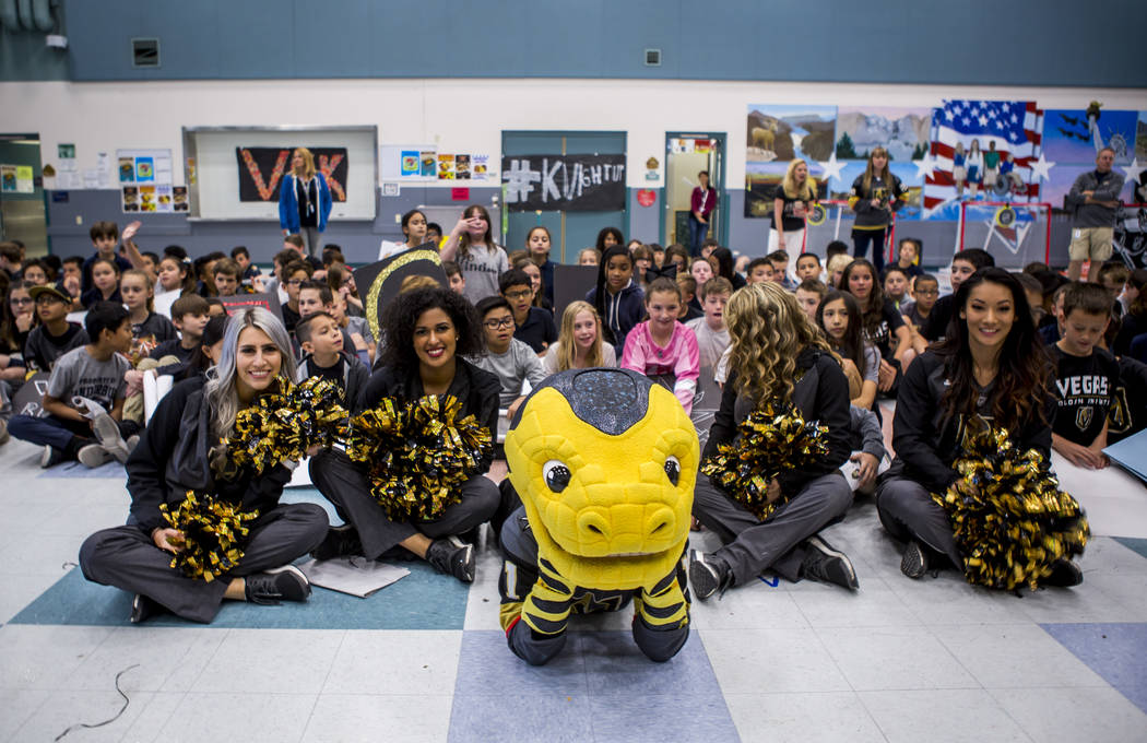 Vegas Golden Knights mascot Chance the Gila monster and Golden Aces cheerleaders sit with the crowd of elementary schoolers during a Golden Knights pep rally for fourth and fifth graders at John C ...