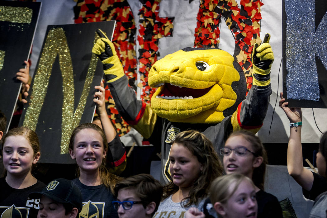 Vegas Golden Knights mascot Chance the Gila monster dances along with an original song about the Golden Knights performed by the choir and instrument ensemble during a pep rally for fourth and fif ...