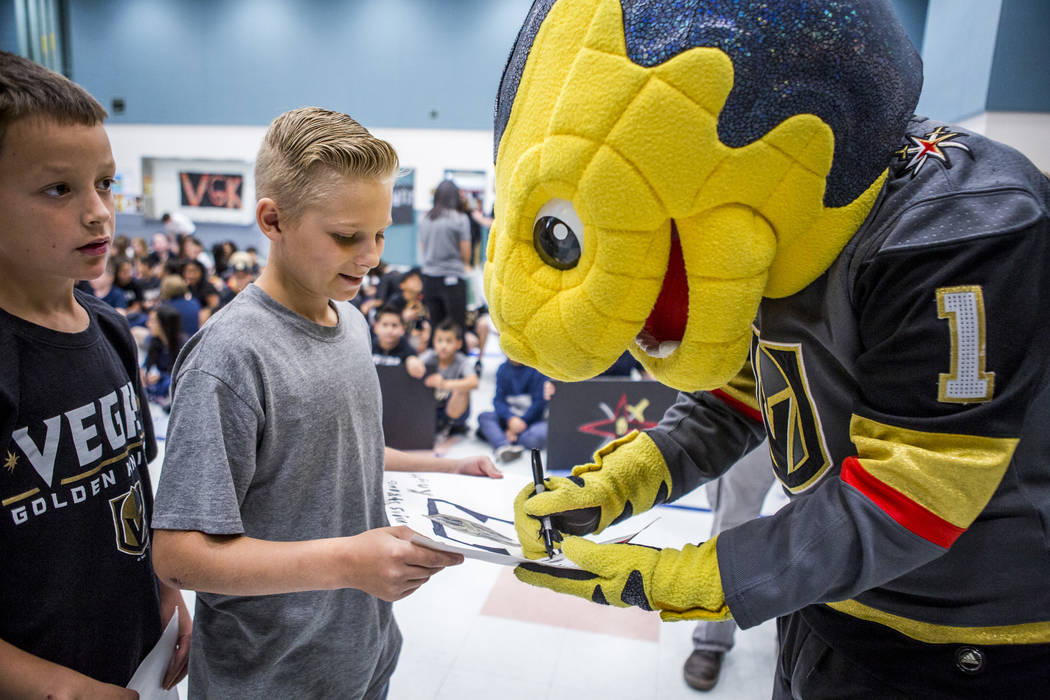 Vegas Golden Knights mascot Chance the Gila monster signs a drawing for fourth-grader Bryson Hansen, 10, during a Golden Knights pep rally for fourth and fifth graders at John C. Vanderburg Elemen ...