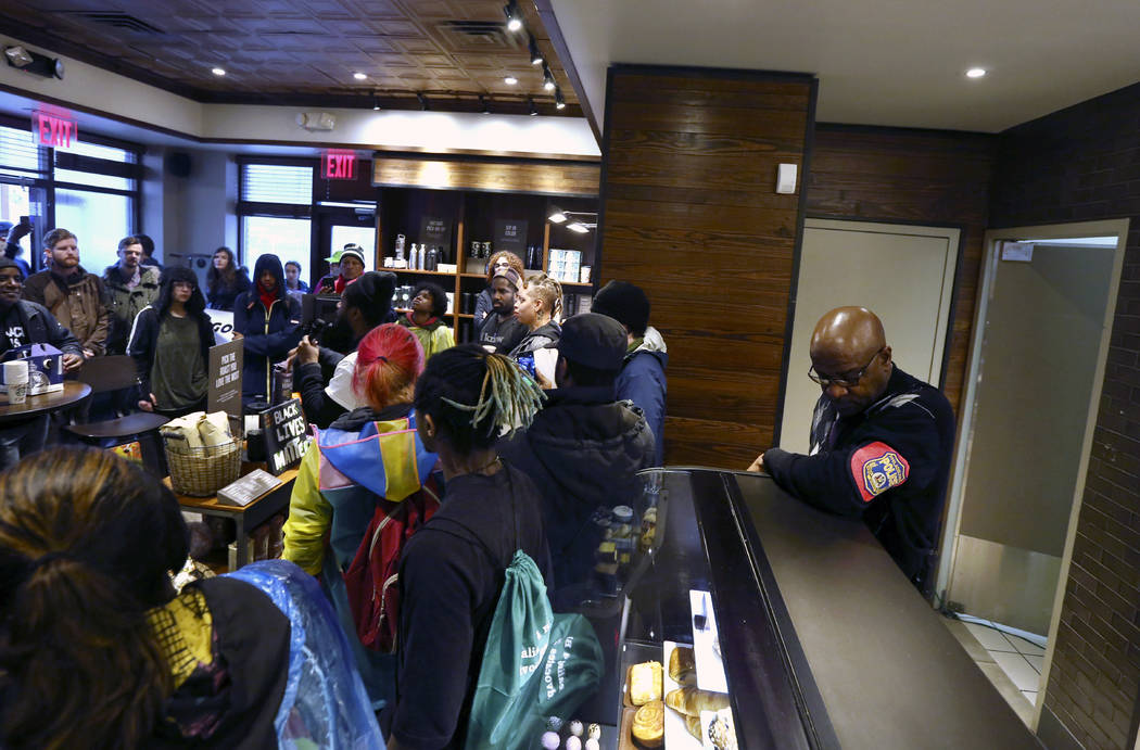 A plain-clothed police officer, right, mans a position behind the counter at the Starbucks that has become the center of protests Monday, April 16, 2018, in Philadelphia. (AP Photo/Jacqueline Larma)