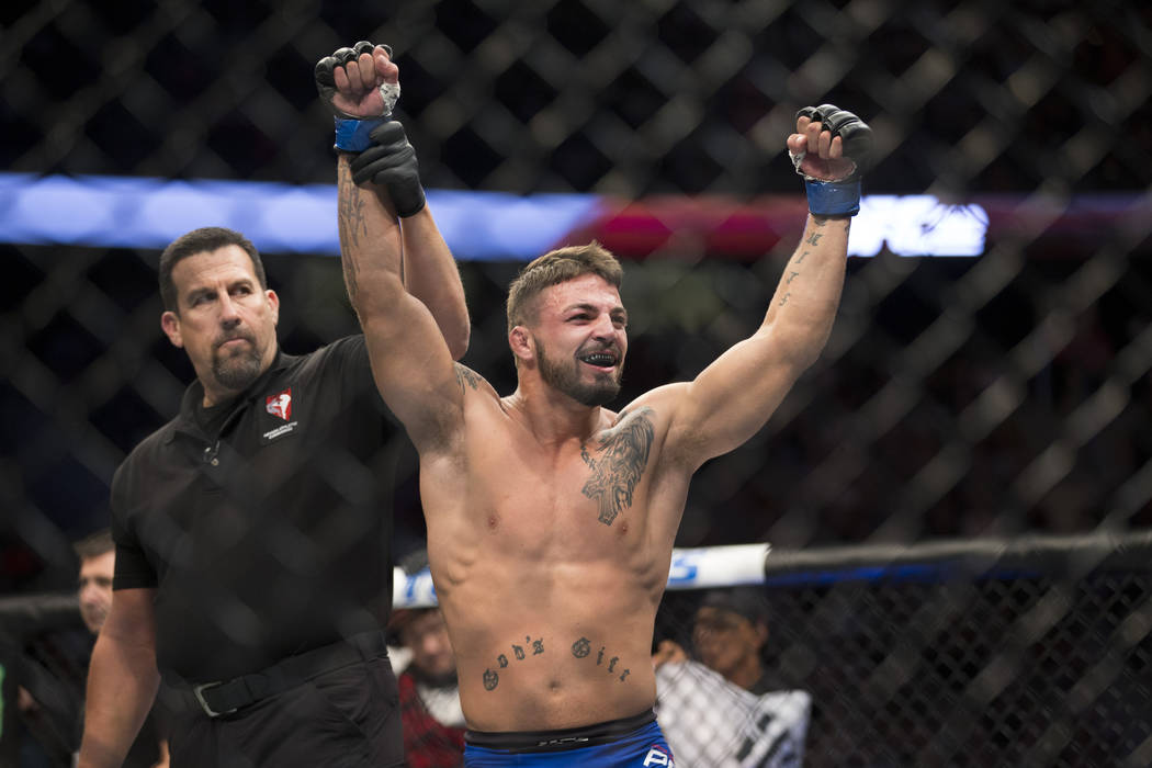 Mike Perry raises his arms in victory after his first round technical knockout against Hyun Gyu Lim in the welterweight bout during UFC 202 at T-Mobile Arena on Saturday, Aug. 20, 2016, in Las Veg ...
