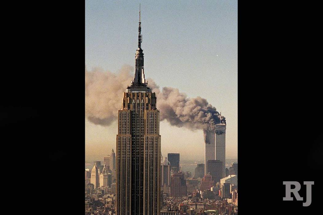 The twin towers of the World Trade Center burn behind New York's Empire State Building in this Sept. 11, 2001 file photo. (Marty Lederhandler/AP)