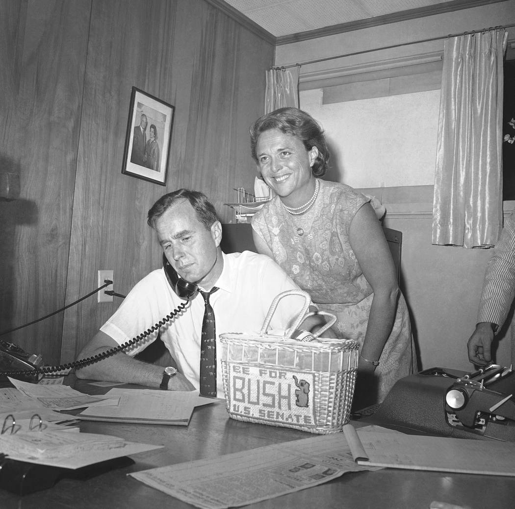 George Bush, candidate for the Republican nomination for the U.S. Senate, gets returns by phone at his headquarters in Houston, Saturday, June 6, 1964 as his wife Barbara, beams her pleasure at th ...