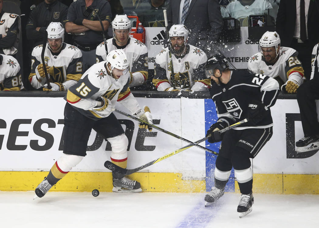 Golden Knights defenseman Jon Merrill (15) and Los Angeles Kings center Trevor Lewis (22) battle for the puck during the first period of Game 4 of an NHL hockey first-round playoff series at the S ...