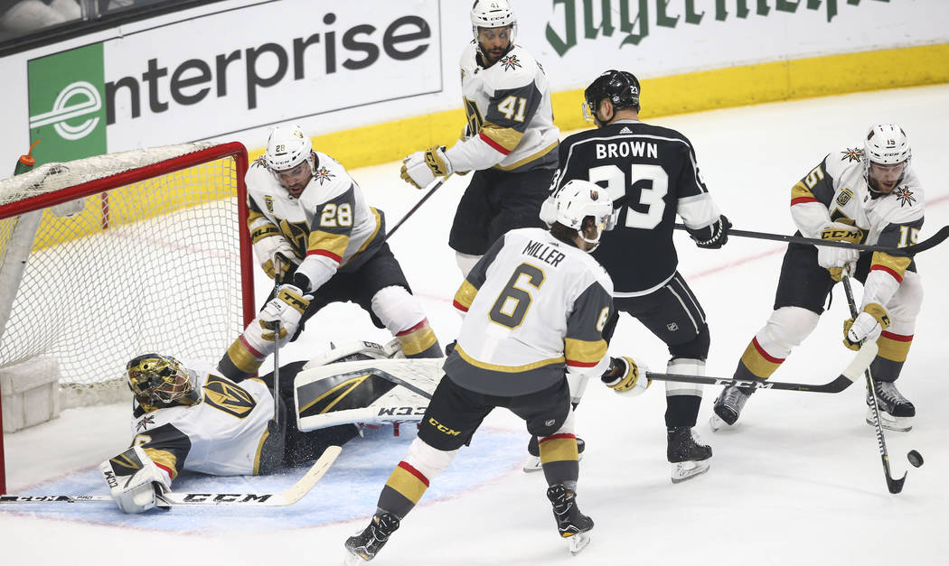Golden Knights goaltender Marc-Andre Fleury (29) falls to the ice as defenseman Jon Merrill (15) goes for the puck while Los Angeles Kings right wing Dustin Brown (23) looks on during the first pe ...