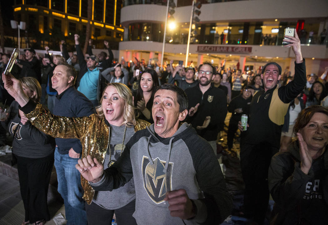 Golden Knights fans Brandon Potts, middle/right, and Shannon Boyd, left, celebrate at a watch party at the Mandalay Bay hotel-casino after Vegas defeated the Los Angeles Kings 1-0 to complete the ...