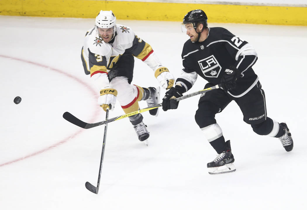 Los Angeles Kings center Trevor Lewis (22) sends the puck into the air as Golden Knights defenseman Brayden McNabb (3) defends during the first period of Game 4 of an NHL hockey first-round playof ...