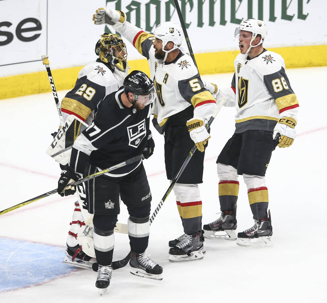 Golden Knights goaltender Marc-Andre Fleury (29), defenseman Deryk Engelland (5) and defenseman Nate Schmidt (88) celebrate after defeating the Los Angeles Kings 1-0 in Game 4 of an NHL hockey fir ...