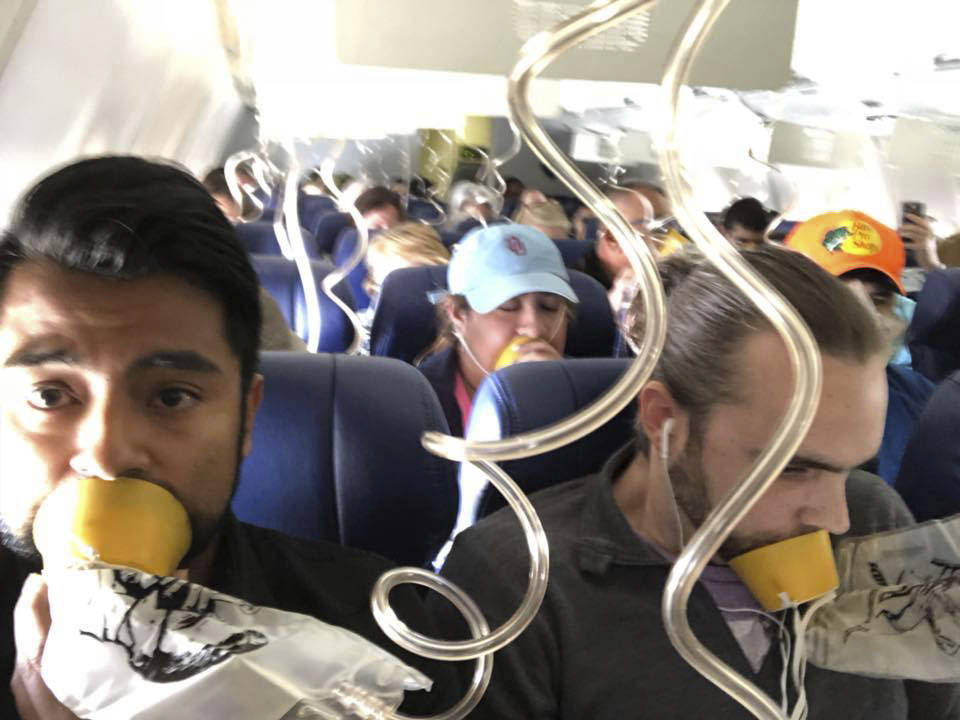 In this April 17, 2018 photo provided by Marty Martinez, Martinez, left, appears with other passengers after a jet engine blew out on the Southwest Airlines Boeing 737 plane he was flying in from ...