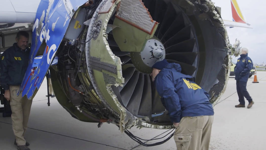 In this Tuesday, April 17, 2018 frame from video, a National Transportation Safety Board investigator examines damage to the engine of the Southwest Airlines plane that made an emergency landing a ...