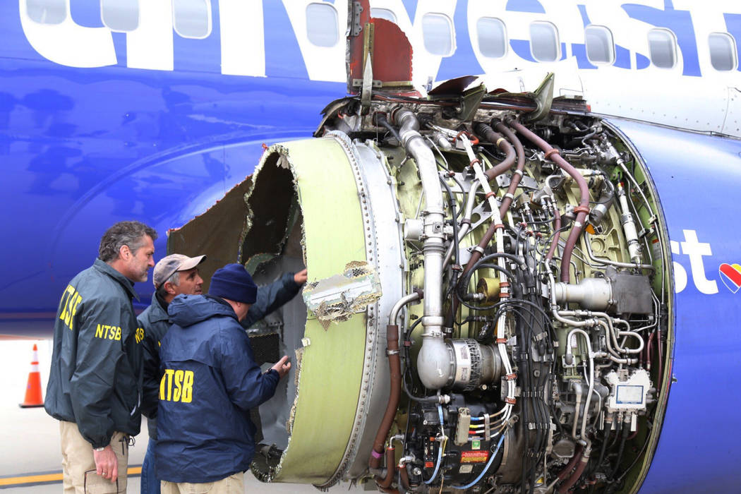 National Transportation Safety Board investigators examine damage to the engine of the Southwest Airlines plane that made an emergency landing at Philadelphia International Airport in Philadelphia ...