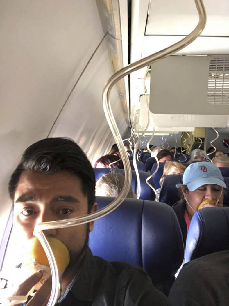 In this April 17, 2018 photo provided by Marty Martinez, Martinez appears with other passengers after a jet engine blew out on the Southwest Airlines Boeing 737 plane he was flying in from New Yor ...