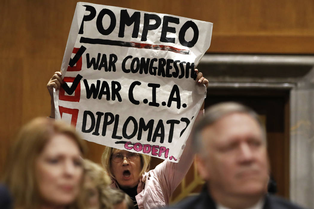 Retired U.S. Army Col. Ann Wright, center, protests the nomination of CIA Director Mike Pompeo, front right, for secretary of state, as he waits to testify before the Senate Foreign Relations Comm ...