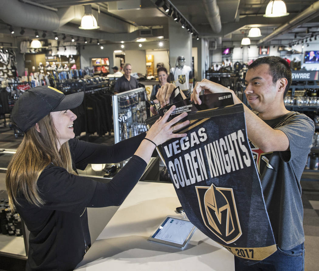 Michael Harlan, right, buys some Golden Knights swag from Anna Sommers on Wednesday, April 18, 2018, at The Arsenal, in Las Vegas. Benjamin Hager Las Vegas Review-Journal @benjaminhphoto
