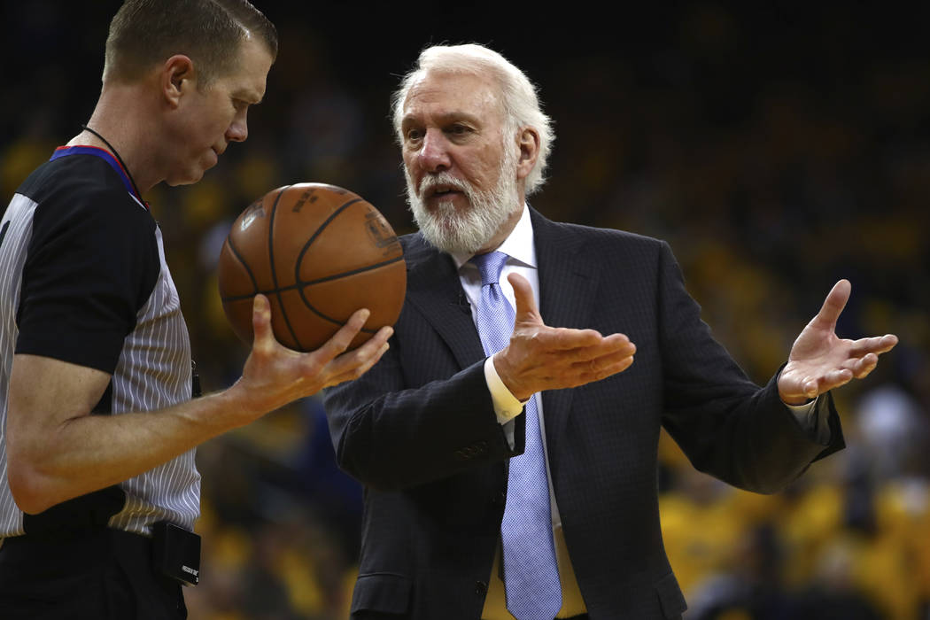 San Antonio Spurs coach Gregg Popovich, right, gestures to a referee during the second half in Game 2 of a first-round NBA basketball playoff series against the Golden State Warriors Monday, April ...