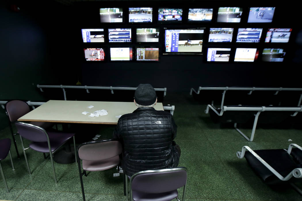 In this Nov. 30, 2017, photo, a man watches simulcast horse races at the Monmouth Park racetrack in West Long Branch, N.J. With banks of TVs tuned to all-sports stations and a spacious bar, the lo ...