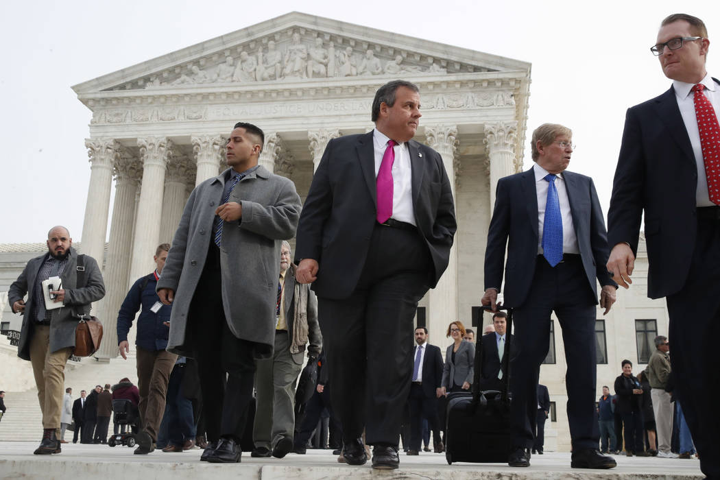 New Jersey Gov. Chris Christie, center, leaves the Supreme Court where a case on sports betting is being heard, Monday, Dec. 4, 2017. (AP Photo/Jacquelyn Martin)