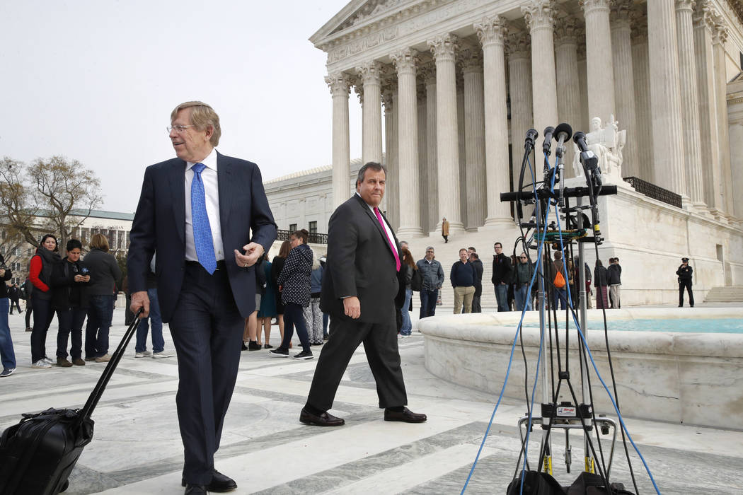 Theodore Olson, left, the lawyer for New Jersey, walks with New Jersey Gov. Chris Christie to attend a news conference after leaving the Supreme Court where a case on sports betting is being heard ...