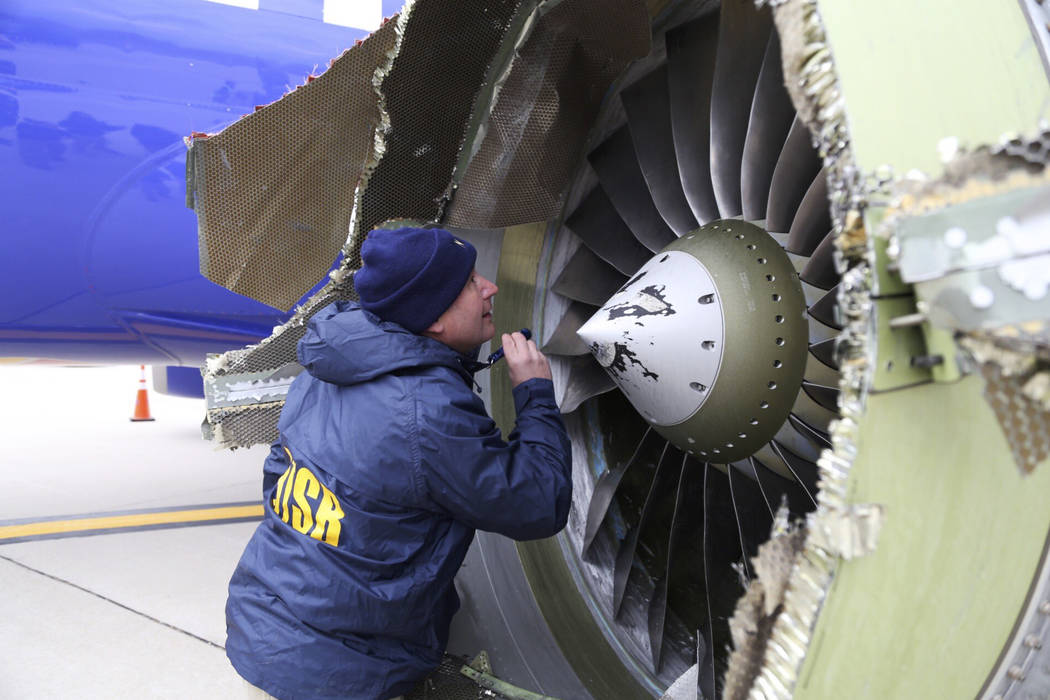 A National Transportation Safety Board investigator examines damage to the engine of the Southwest Airlines plane that made an emergency landing at Philadelphia International Airport in Philadelph ...