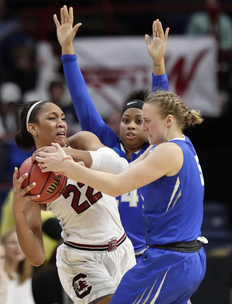 South Carolina's A'ja Wilson (22) fights for control of the ball with Buffalo's Katherine Ups (5) and Cierra Dillard (24) during the second half in a regional semifinal at the NCAA women's college ...