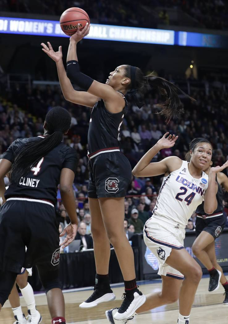 South Carolina's A'ja Wilson, center, drives past Connecticut's Napheesa Collier (24) during the first half of a regional final at the a women's NCAA college basketball tournament Monday, March 26 ...